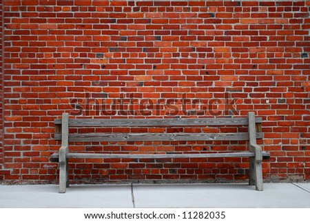 Old bench against brick wall - stock photo