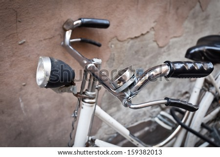 Old Bicycle Leaning on a wall in a street in Ferrara (Emilia-Romagna, Italy). - stock photo