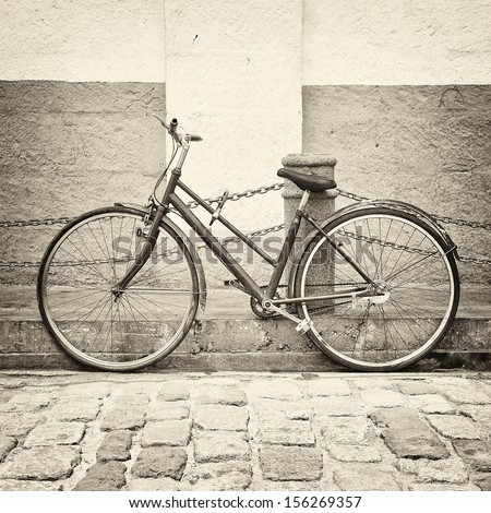 Old bicycle on ancient street in black and white style - stock photo