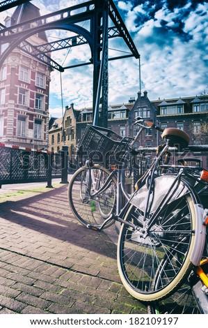 Old bicycle on bridge. Amsterdam cityscape - stock photo