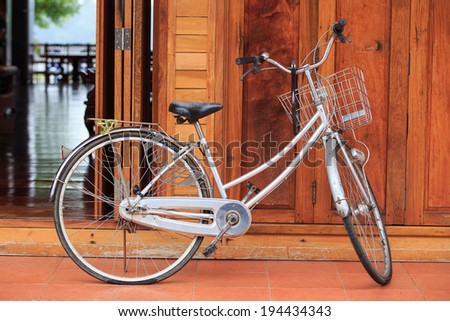 Old bicycle on vintage wooden house wall - stock photo