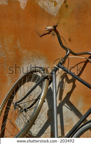 Old bicycle resting against a contrasting orange wall with a shadow - stock photo