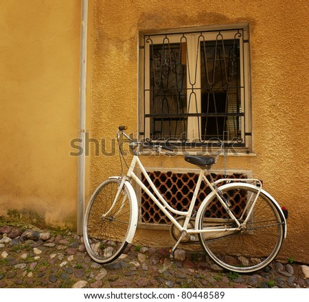 Old bicycle standing against a wall under a window. - stock photo