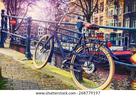 Old bicycle standing next to canal. Amsterdam cityscape - stock photo
