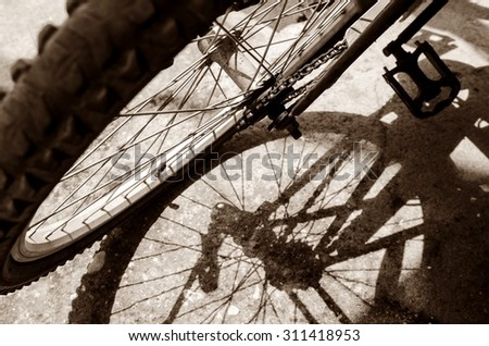 Old bicycle wheel casting a shadow on the ground, sepia tone. - stock photo