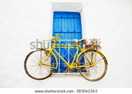 Old bicycle with a basket leaning against a wall in Greece - stock photo