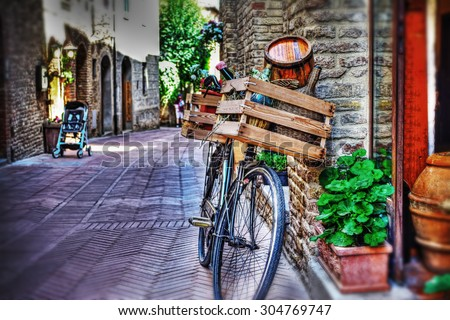 old bike with wooden case against a brick wall in San Gimignano, Italy - stock photo
