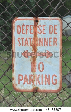 Old bilingual No Parking sign - stock photo