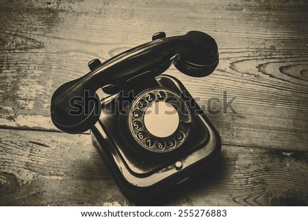 Old black phone with dust and scratches, isolated on wooden retro floor - retro picture and retro technology - stock photo