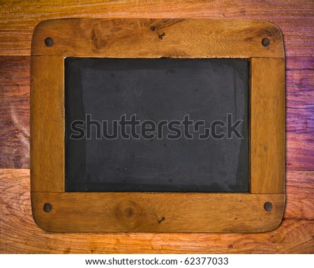 Old blackboard with a wooden frame on wood wall. - stock photo