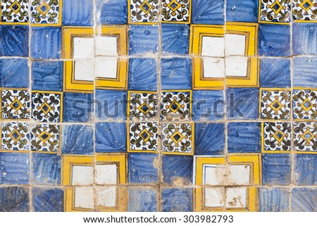 Old blue and yellow azulejos on the building's exterior in Cascais, Portugal. - stock photo