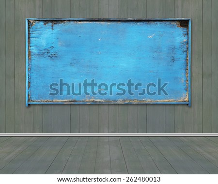 Old blue blank weathered noticeboard on dark green wooden wall and floor background - stock photo
