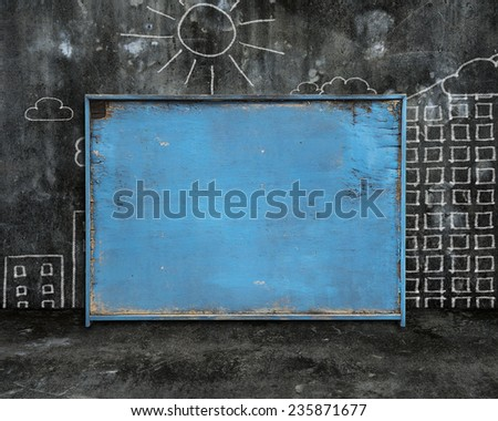 old blue blank weathered noticeboard with sun city buildings doodles on dark mottled concrete wall and floor background - stock photo