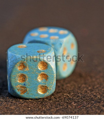 Old blue dice with golden numbers over black background - stock photo