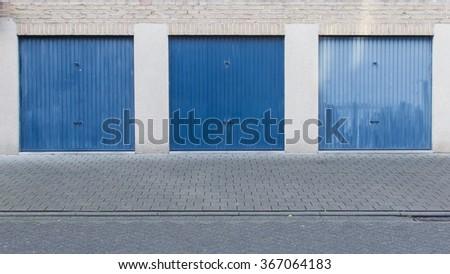 Old blue door of a garage, empty street - stock photo