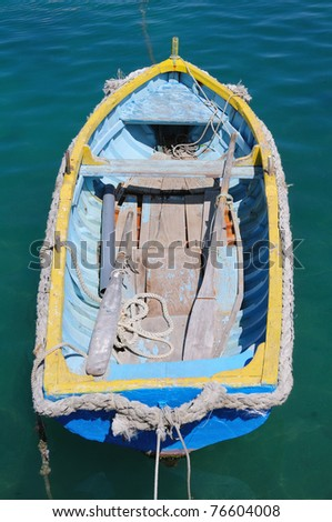 Old blue fishing boat floating on the water - stock photo
