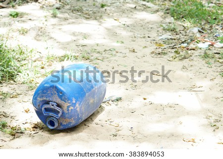 Old Blue gallon on the ground - stock photo