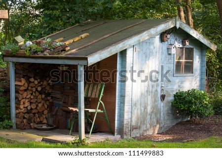 old blue garden shed and fire wood - stock photo