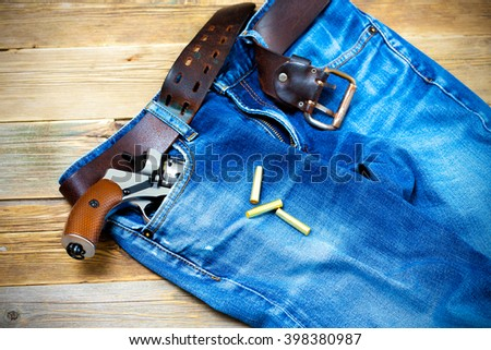old blue jeans with a leather belt and silver revolver in his pocket - stock photo