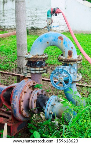 old blue piping of water pump against green grass - stock photo