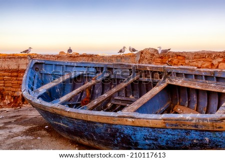 Old blue rowboat. Location:  The picturesque fishing village of Essaouira, Morocco. Room for text. - stock photo