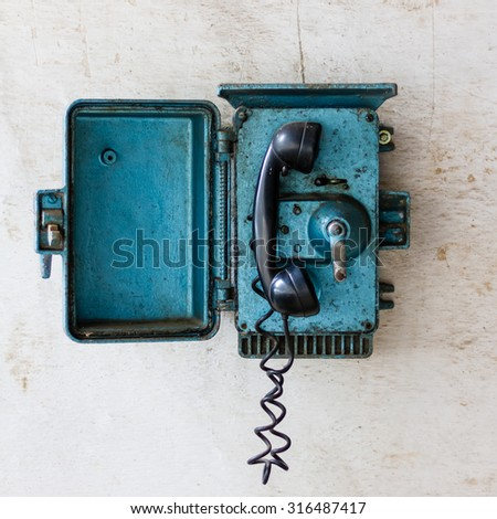 Old blue telephone in an abandoned warehouse. Communication concept. - stock photo