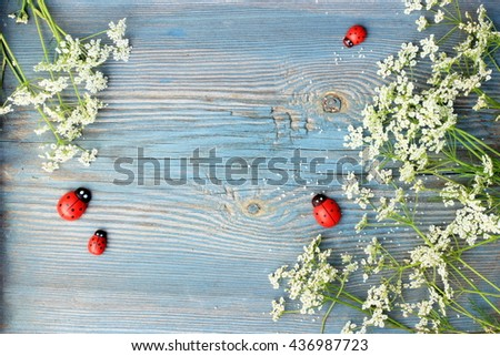 Old blue wooden background with frame made of small white flowers and decorative red wooden ladybirds. Copy space with floral and handmade wooden decor elements. Rustic design - stock photo