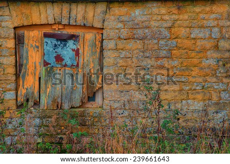 Old boarded up window in a stone farm building - stock photo