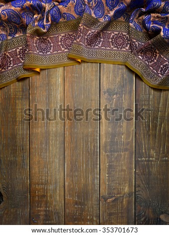 Old boards and fabric with traditional east ornaments paisley. Ethnic background. - stock photo