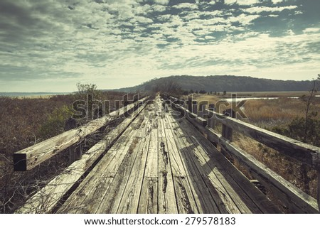Old boardwalk by the ocean. Outdoors summer concept. Light vintage green post processed - stock photo