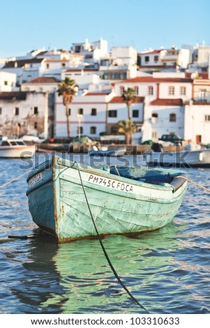Old boat in the bay Ferragudo, Portugal. Seascape - stock photo