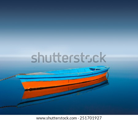 Old boat on calm river - stock photo