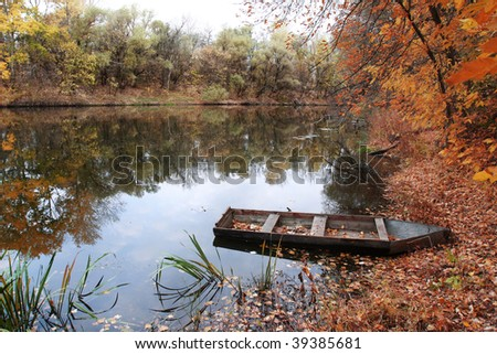 old boat on the forest river - stock photo