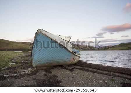 old boat on the shore of a lake on the isle of skye - stock photo