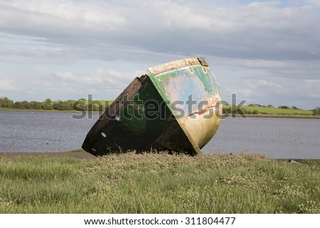 old boat sitting on the side of an estuary  - stock photo