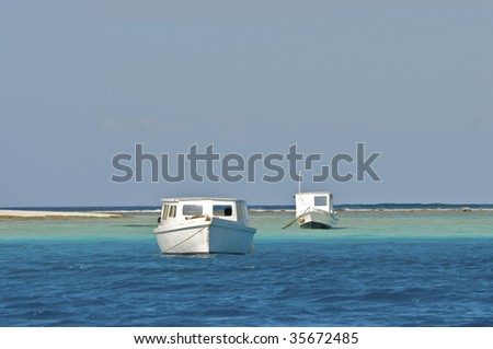 old boats docked in beautiful blue harbour - stock photo