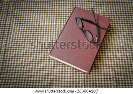 old book and glasses on tablecloth - stock photo