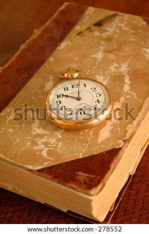 Old book and old pocket watch. - stock photo