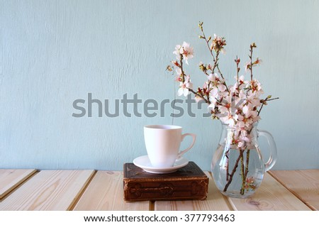 old book, cup of coffee next to spring white flowers on wooden texture - stock photo