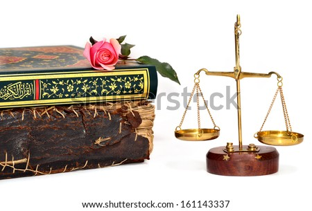 old book, holy koran on rose and justice scales - stock photo