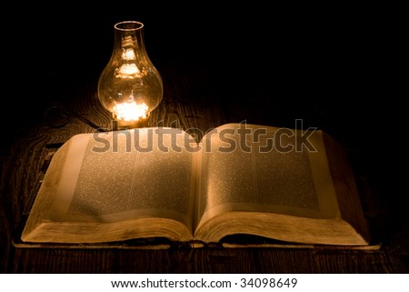 Old book illuminated by the warm light of an old  lamp. - stock photo