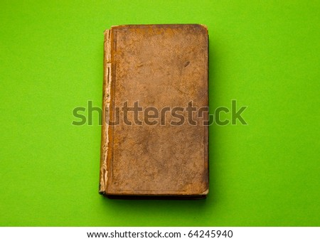 Old book isolated on green - stock photo