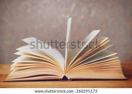 old book on a wooden background, toned image - stock photo