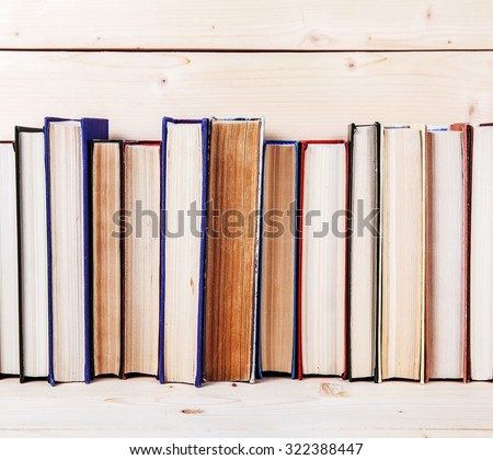 old book shelf blank spines, empty binding stack on wood texture background - stock photo