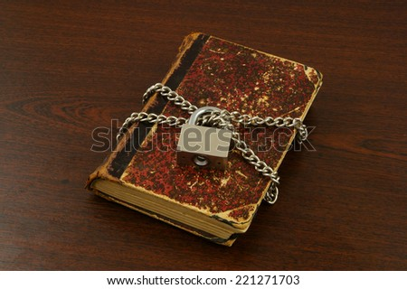 Old book with chain and padlock on wooden table - stock photo
