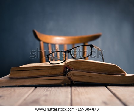 Old books and glasses  on a wooden table of  teacher. Focus on glasses - stock photo