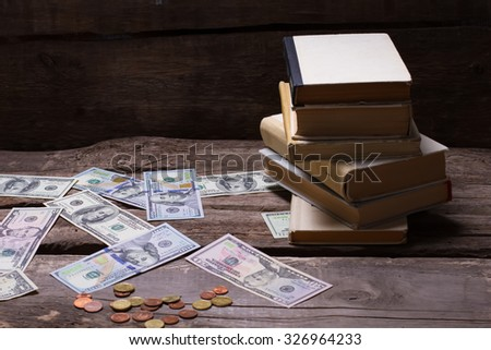 Old books and money on a vintage wooden background. Dollars and coins scattered on a retro background. - stock photo