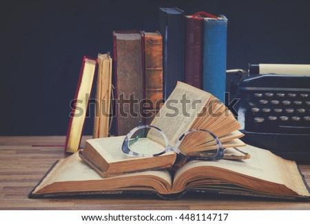 Old books, glasses and typewriter - writting and publishing concept , retro toned - stock photo