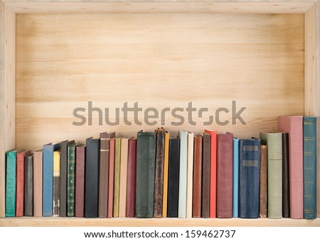 Old books on a wooden shelf.  - stock photo