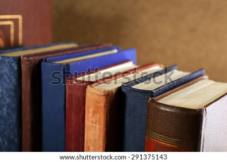 Old books on shelf, close-up, on dark wooden background - stock photo